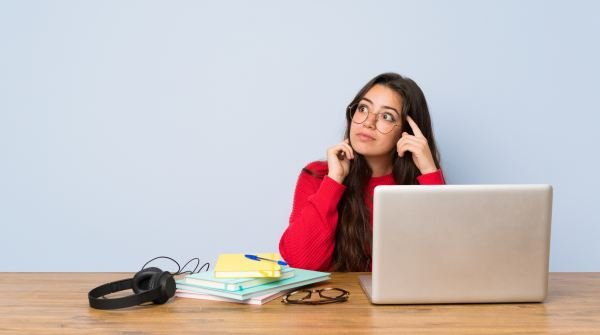 Teenager student girl studying in a table having doubts and thinking