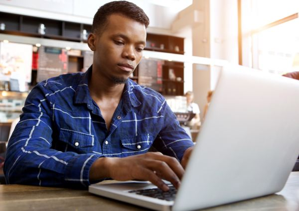serious young man sitting in cafe using laptop