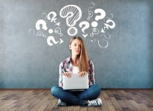 Attractive young woman sitting on wooden floor with laptop and drawn question marks above on concrete wall. Confusion concept