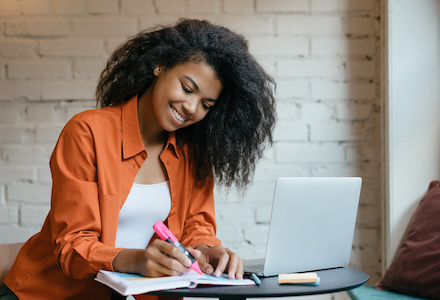 Young attractive African American business woman working project, planning strategy, taking notes in modern office. University student studying, learning language, using laptop computer and internet