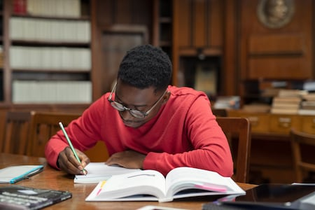 University student wearing spectacles studying in library. Young african man taking notes from book while sitting in the library. Focused casual guy writing notes during homework.