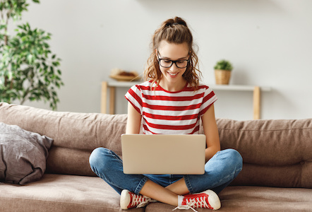 Cheerful young female freelancer in glasses and casual clothes focusing on screen and interacting with laptop while sitting alone on soft couch in light modern living room