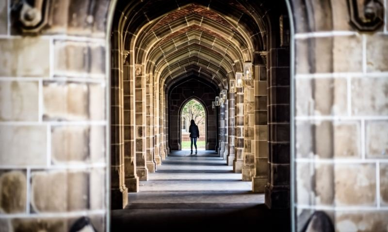 A stone arch hallway at a university with unidentified female in the distance
