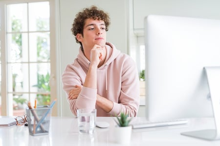 Young student man using computer serious face thinking about question, very confused idea